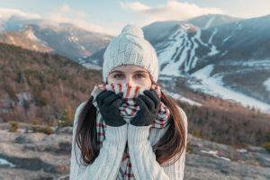 A woman, winter, beanies, a winter scarf, a pair of winter gloves, smiling, mountains