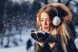 a woman, earmuffs, a winter coat, winter gloves, winter, snow