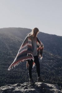 a woman, mountain, sunlight, a wrap cardigan sweater, leggings,